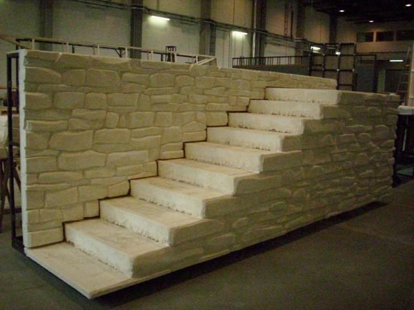 mit plastischer Sandsteinoberfläche belegter Teil von Treppenwagen und Rückwand